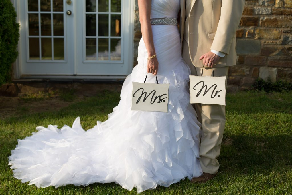 bride and groom holding mr and mrs signs