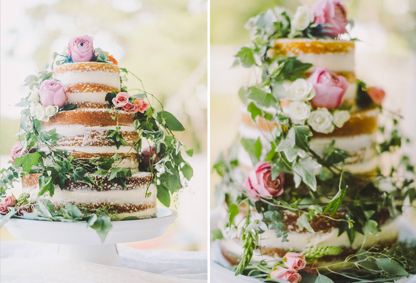naked wedding cake with foliage and flower blooms