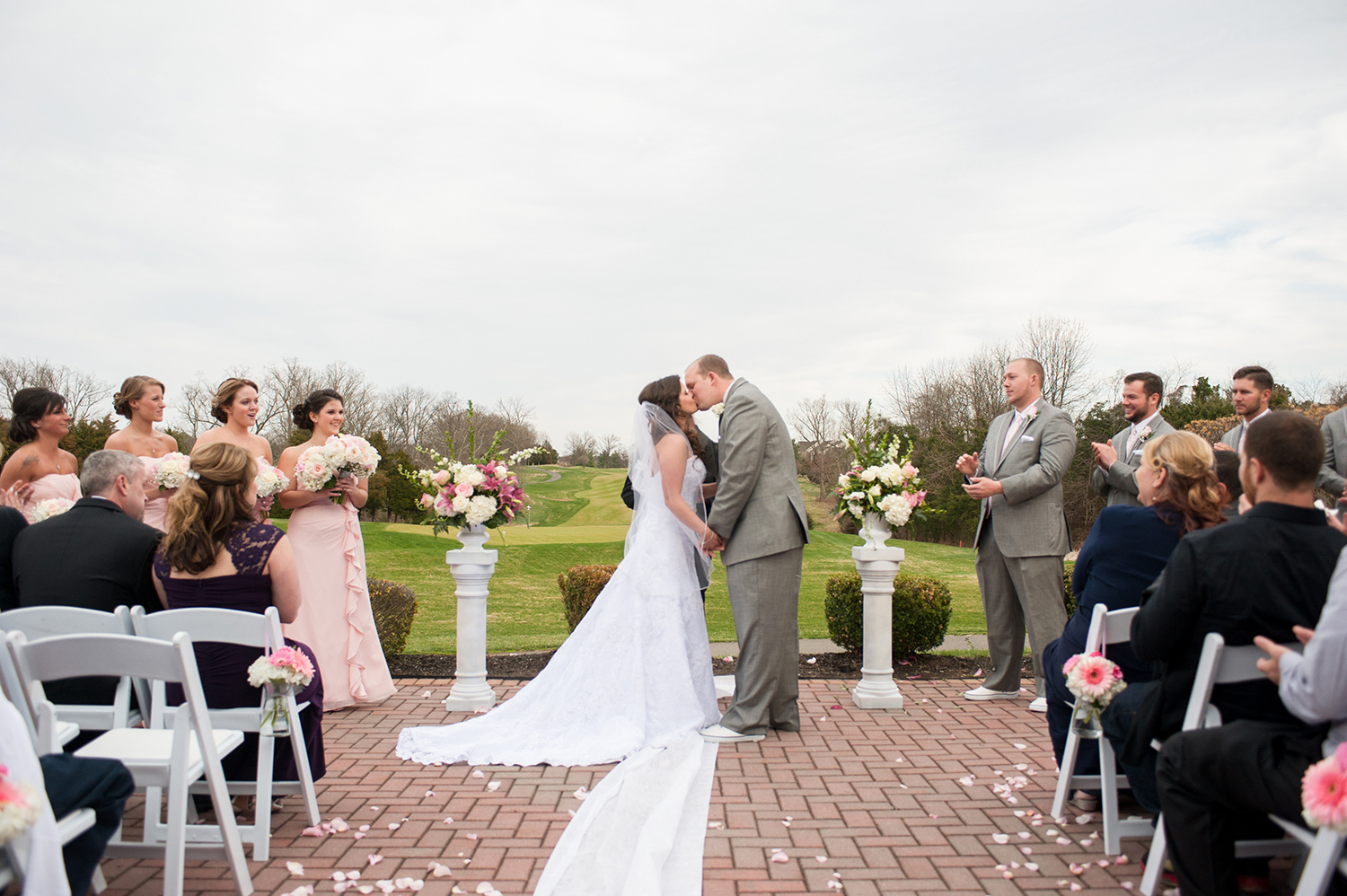 bride and groom first kiss in outdoor wedding ceremony