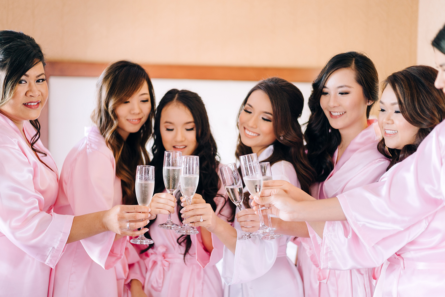bride and bridesmaids toasting champagne before wedding