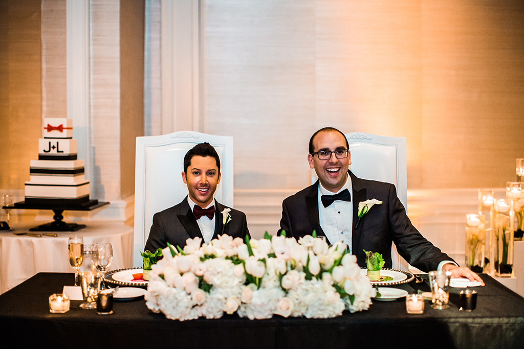 gay couple at sweetheart table at wedding reception