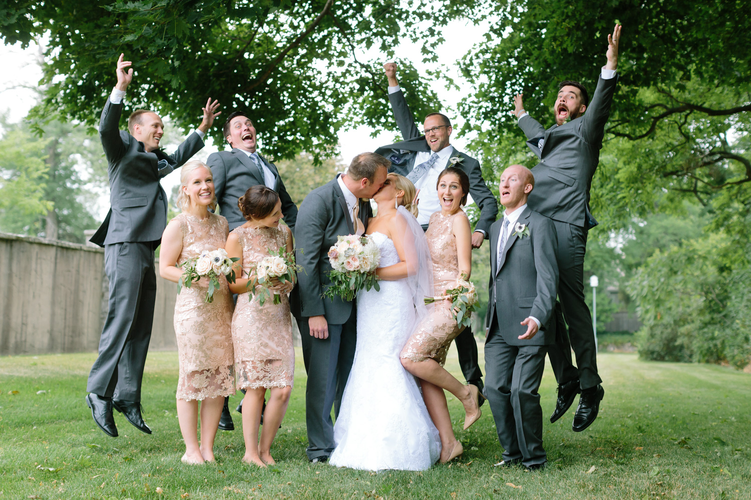 BridalPulse - Golf Lovers' Country Club Wedding - bride groom kiss with bridal party excited in background