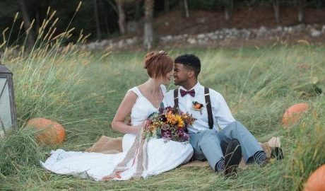 bride-and-groom-sit-on-grass-with-pumpkins