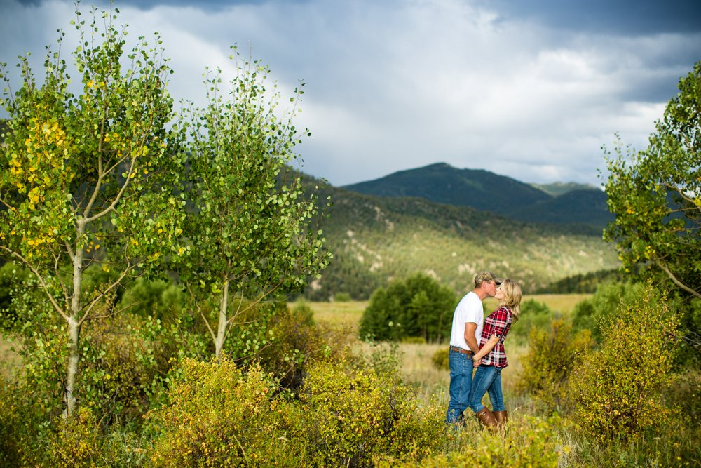 BridalPulse - Rustic and Romantic Colorado Engagement Shoot-Photography by Haley Allen Photography-the couple kisses near a mountain