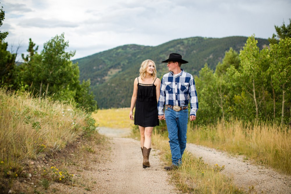 BridalPulse - Rustic and Romantic Colorado Engagement Shoot -Photography by Haley Allen Photography - Couple walks down a dirt road smiling